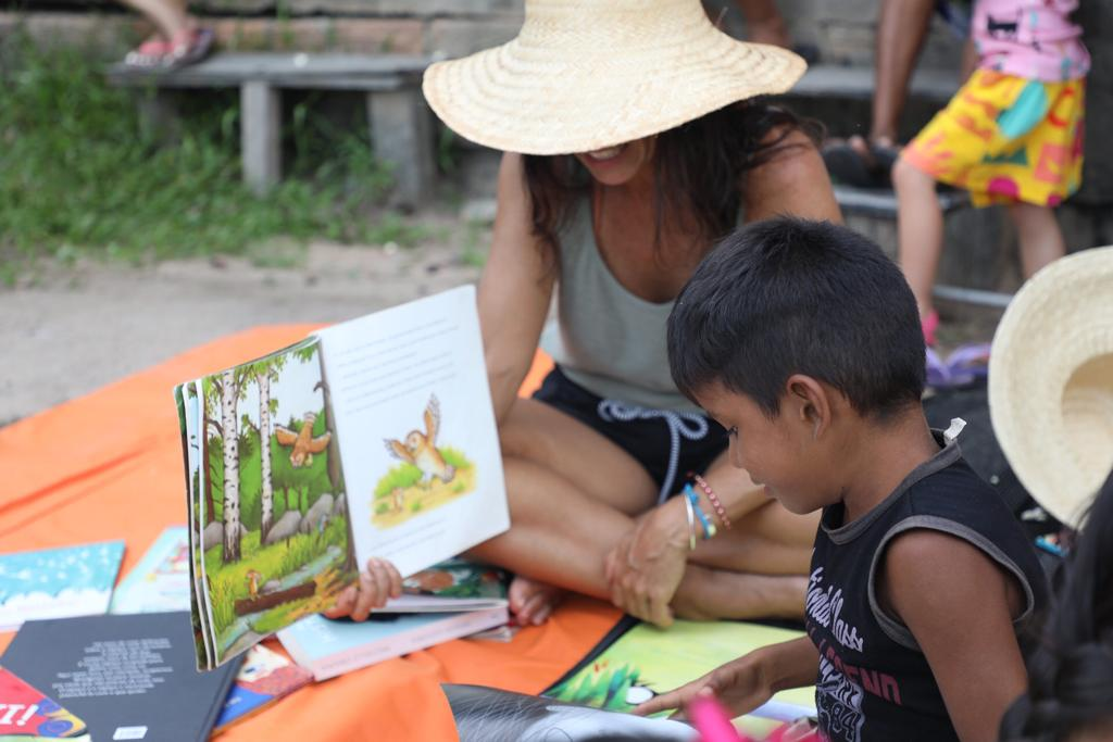 Woman reading a book together with a child